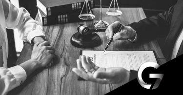 mãos sobre a mesa com objetos jurídicos