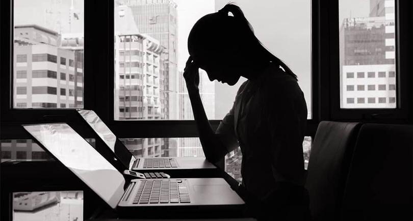 imagem mostrando uma mulher em frente ao computador com a mão na cabeça e olhando para baixo