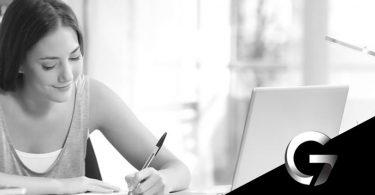 imagem de uma mulher estudando com um notebook em cima de mesa